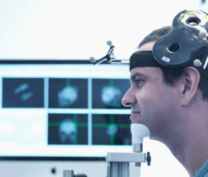 A male patient undergoing a session of transcranial magnetic stimulation